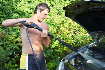 Young men cleaning car with pressured water outdoors photo
