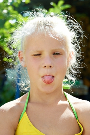Portrait of little girl showing the tongue