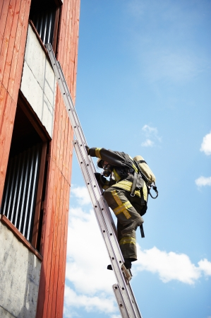 Firefighter climb on fire stairs to window photo
