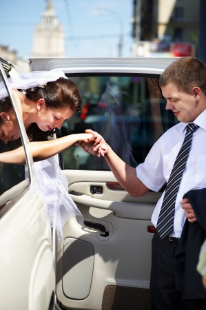 Gallant groom helping his bride out of a wedding limousine on sunny summer day photo