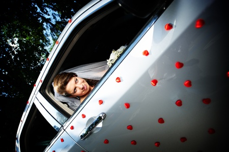 Beautiful bride in a wedding limousine with red little hearts photo