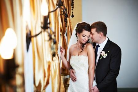 Элегантный жених и невеста в день свадьбы в роскошном дворце Фото со стока