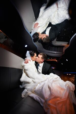 Gentle kiss bride and groom in wedding limousine photo