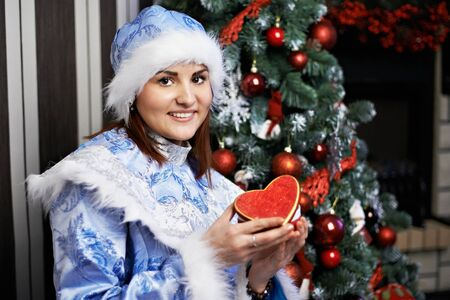 Young woman with a Christmas costume Snow Maiden against decorated Christmas tree photo