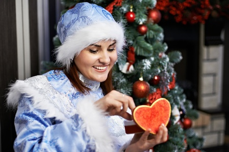 Happy woman with Christmas costume Snow-Maiden receives gift photo