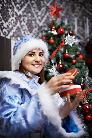 Young woman with a Christmas costume Snow-Maiden against decorated Christmas tree photo