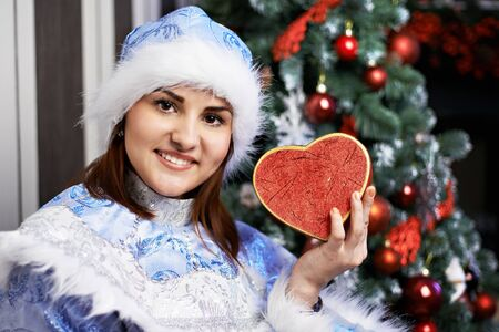 Young woman with a Christmas costume with red heart near beauty tree photo