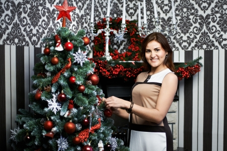 Beautiful young woman near the holiday Christmas tree and decorated fireplace photo