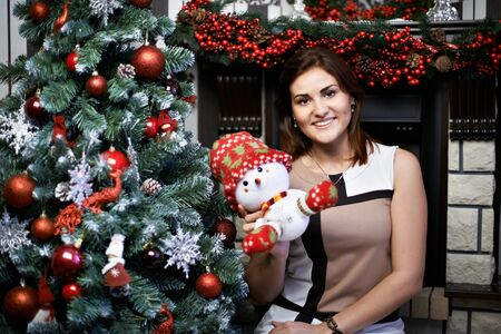 Beautiful young woman and snowman near the holiday Christmas tree and decorated fireplace photo