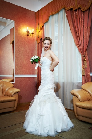 view of an elegant red couch: Happy beautiful bride in interior wedding palace for solemn registration