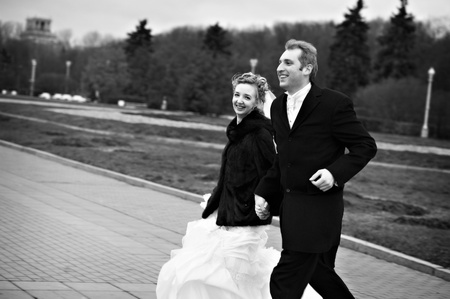 Happy bride and groom run on garden. Black and white vintage style photo