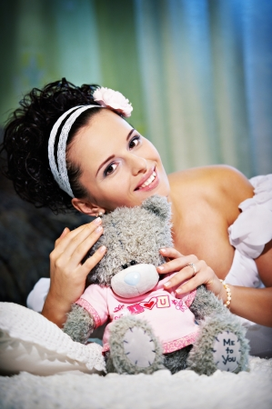 Portrait beautiful bride with teddy bear on white bed in wedding day photo