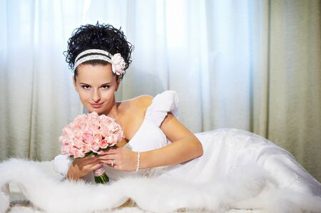 Portrait beautiful bride with bouquet of flowers on white bed in wedding day photo