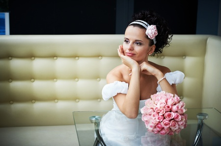 Portrait beautiful bride with bouquet of flowers on modern interior in wedding day photo