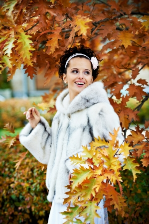 Style happy bride in autumn park on wedding walk photo