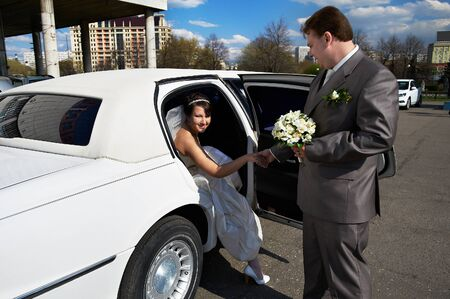 Happy bride and groom out of wedding limousine in city photo