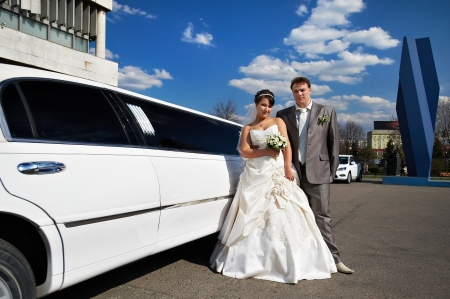 Happy bride and groom near wedding limo in summer day 스톡 콘텐츠