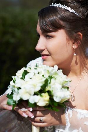 looking sideways: Happy bride with flowers looking sideways Stock Photo