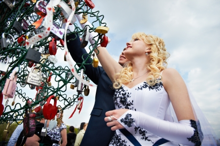 Happy bride and groom at wedding walk on Luzhkov bridge in Moscow photo