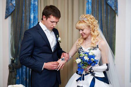solemn: Elegant groom wears wedding ring happy bride. Solemn registration of marriage. Stock Photo