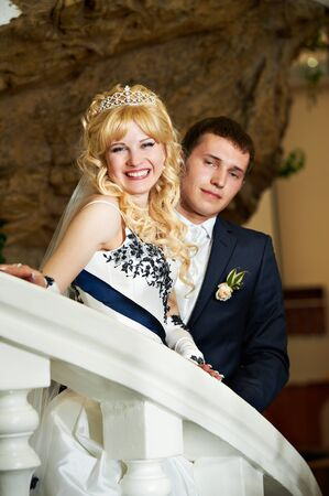 Happy bride and groom on a white ladder on wedding day photo
