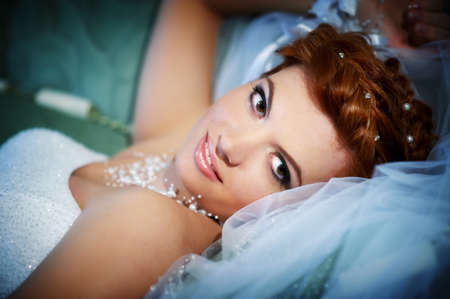 Portrait beautiful bride lying on bed in wedding day photo