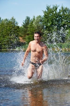 caucasian water drops: Strong man running on the water at beach in summer days Stock Photo