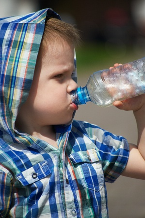 Little boy drinking from plastic bottle on a hot day photo