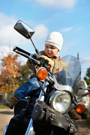 Little boy sits on a big motorcycle photo