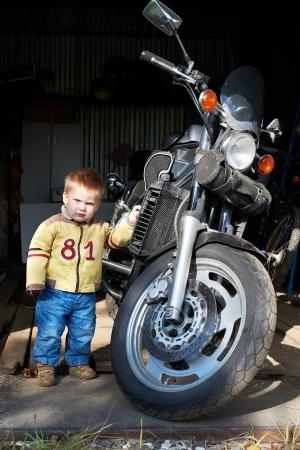 Маленький мальчик стоит возле большой мотоцикл в гараже