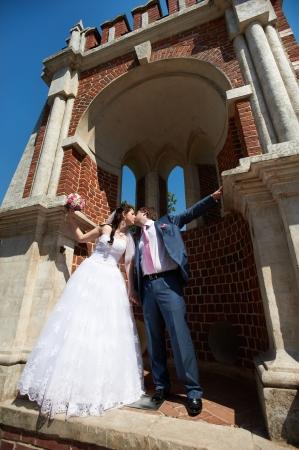 Romantic kiss bride and groom at wedding walk near ancient brick building photo