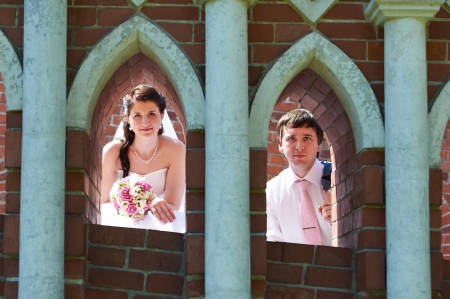 Happy bride and groom in windows of brick wall in wedding walk photo