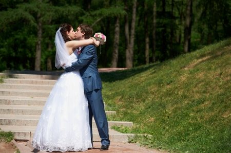 Happy Bride and groom kissing at wedding walk in park photo
