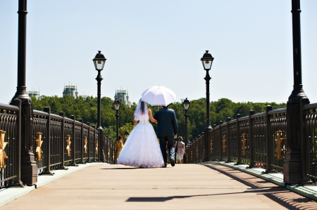 Happy bride and groon on walking in park photo
