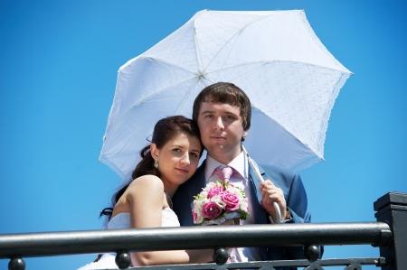Happy bride and groom with umbrella at wedding walk photo