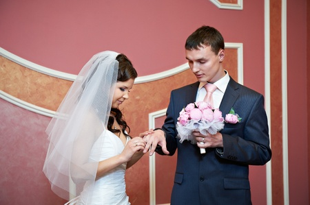 Beauty bride wears wedding ring on finger of elegant groom. Solemn registration of marriage. photo