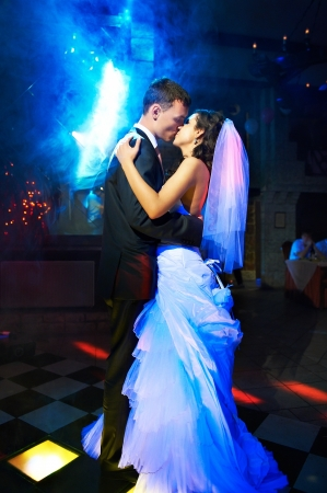 Kiss and dance young bride and groom in dark banqueting hall photo