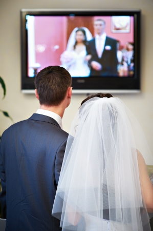 Bride and groom watch the video of his solemn registration Фото со стока