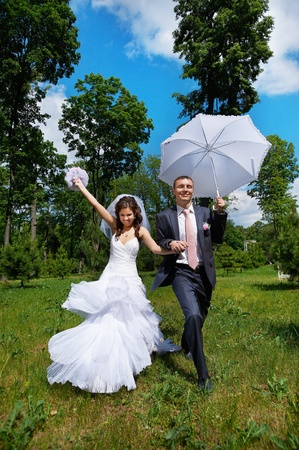 Happy groom and happy bride with umbrella run on wedding walk in park photo