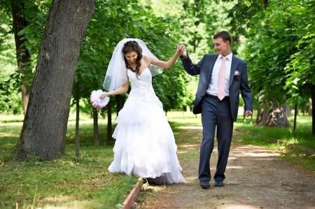 Счастливые жених и невеста в тенистые аллеи на свадьбе прогулка