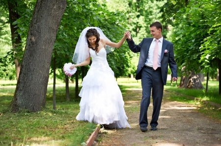 Happy bride and groom in shady alley on wedding walk
