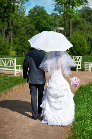 Happy bride and groom goes along the path on wedding walk photo