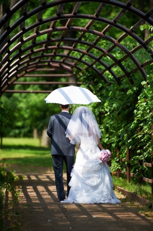 Happy bride and groom goes along the arch on wedding walk 写真素材