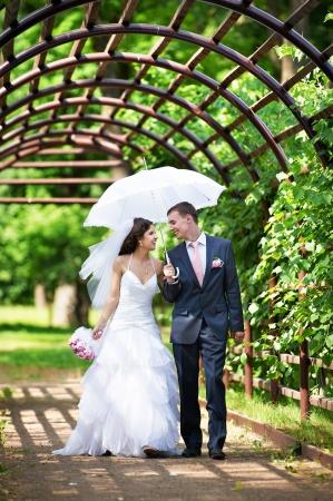 Happy bride and groom goes along the arch on wedding walk Standard-Bild