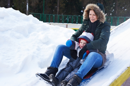 Mother and son sledding down the hill, snow, winter  photo