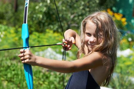 女の子は、自然の背景に弓を撮影します。 写真素材