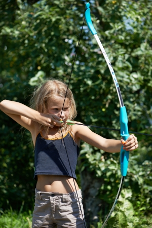 Girl aim with bow on background of nature photo