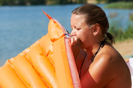 Woman inflates mattress for swimming closeup