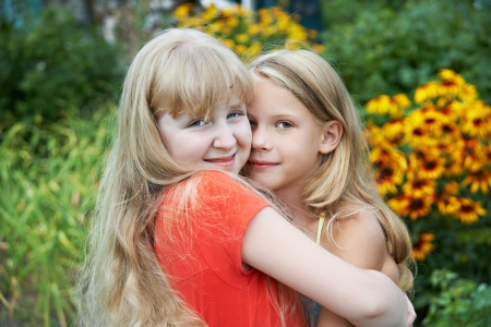 Sisters hugging in garden photo