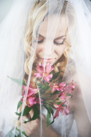 Portrait beautiful bride with bouquet of lilies photo